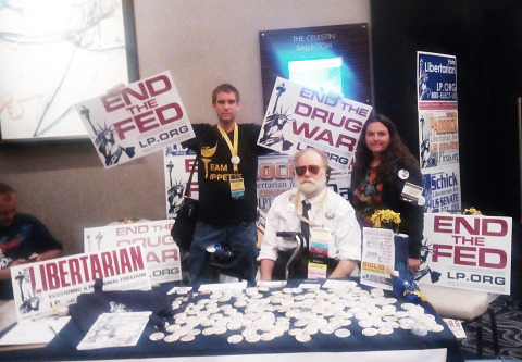 Our signs at the Libertarian Statue Press table at NOLA 2018